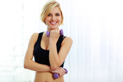 Fit woman holding dumbbells and smiling at camera Stock Photo