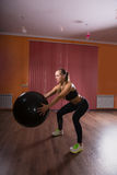 Fit Woman Holding Fitness Ball While Squatting Royalty Free Stock Photos
