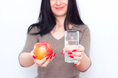 Fit woman holding in hands glass of water and fresh green apple. Stock Photos