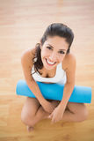 Fit woman holding her exercise mat sitting and smiling at camera Royalty Free Stock Image