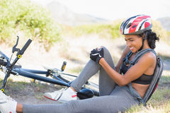 Fit woman holding her injured knee after bike crash Royalty Free Stock Photos