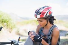 Fit woman holding her injured knee after bike crash Stock Image