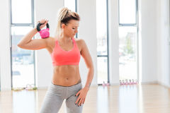 Fit woman holding a kettlebell after finished workout. Stock Photography