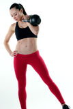 Fit woman holding a kettlebell. Image of a fitness model holding a kettlebell in the rack position Royalty Free Stock Photos