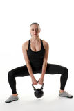 Fit woman holding a kettlebell in a wide squat position. Image of a fitness model doing a kettlebell squat stock photo