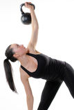 Portrait of fitness model. Portrait of female fitness model in dark top and pants straining to hold  a heavy kettlebell high above her head, white background Stock Photo