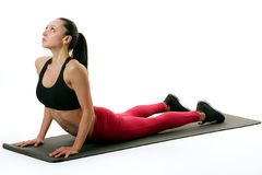 Fit woman holding a lower back stretch. Image of a fitness model doing a lower back yoga stretch Stock Photography