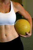 Fit woman holding a medicine ball. With tight abs Royalty Free Stock Photo