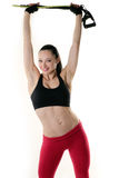 Fit woman holding an resistance band overhead and smiling. Image of a fitness model with a smile on her face Royalty Free Stock Photography