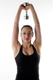 Fit woman holding a single dumbbell overhead. Image of a fitness model holding a weight Stock Images
