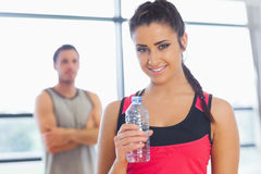 Fit woman holding water bottle with friend in background in exercise room Royalty Free Stock Photo