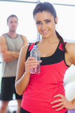Fit woman holding water bottle with friend in background in exercise room Royalty Free Stock Photos