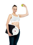 Fit woman holding weighing machine and green apple Stock Images