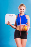 Fit woman holds weight scale grapefruit Royalty Free Stock Image