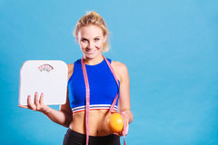 Fit woman holds weight scale grapefruit. Loosing weight, diet and healthy nutrition. Fit fitness woman with measure tape holding weight scale in one and stock photography