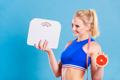 Fit woman holds weight scale grapefruit Royalty Free Stock Photography