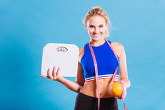 Fit woman holds weight scale grapefruit Royalty Free Stock Photo