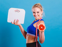 Fit woman holds weight scale grapefruit Stock Image