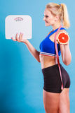Fit woman holds weight scale grapefruit Royalty Free Stock Images
