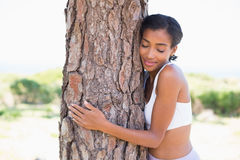 Fit woman hugging a tree Stock Images