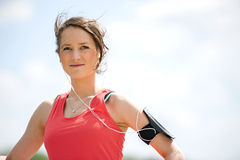 Fit woman jogger resting after run listening music. Royalty Free Stock Photos