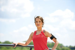 Fit woman jogger resting after run listening music. Royalty Free Stock Photography
