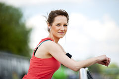 Fit woman jogger resting after run listening music. Stock Image