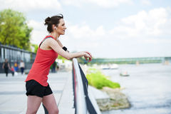 Fit woman jogger resting after run listening music. Royalty Free Stock Image