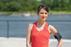 Fit woman jogger resting after run listening music. Smiling. Royalty Free Stock Photography