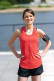 Fit woman jogger resting after run listening music. Smiling. Royalty Free Stock Photos