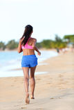 Fit Woman Jogging On Beach - Rear View Stock Image
