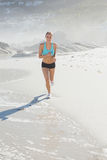 Fit woman jogging on the beach smiling at camera Royalty Free Stock Photo