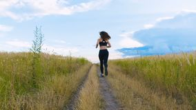 Fit Woman Jogging Exercising Running Cardio outdoor at summer field. Workout Female Runner. Fit Woman Jogging Exercising Running Cardio outdoor. Workout Female stock video