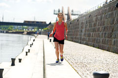 Fit woman jogging by the river. Stock Photos