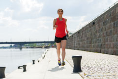 Fit woman jogging by the river. Royalty Free Stock Photography