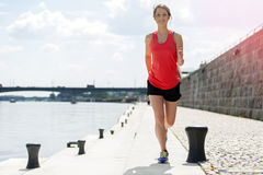 Fit woman jogging by the river. Royalty Free Stock Images