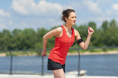 Fit woman jogging by the river. Stock Photo