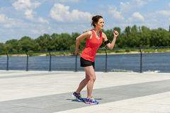 Fit woman jogging by the river. Royalty Free Stock Image