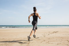 Fit woman jogging on the sand Stock Images