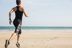 Fit woman jogging on the sand Stock Photography