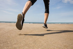 Fit woman jogging on the sand Stock Photos