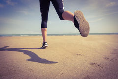 Fit woman jogging on the sand Stock Photo