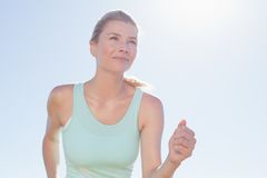 Fit woman jogging and smiling Stock Photo