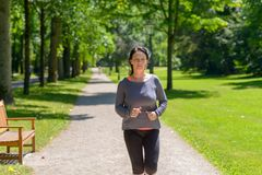 Fit woman jogging towards the camera. In a park with a look of concentration in a healthy active lifestyle concept stock photos