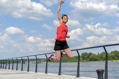 Fit woman jump happy of victory winns. Royalty Free Stock Images
