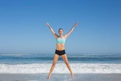 Fit woman jumping on the beach with arms out Royalty Free Stock Image