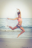Fit woman jumping on the beach Stock Photo