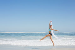 Fit woman jumping gracefully on the beach with scarf Stock Photography