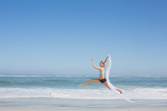 Fit woman jumping gracefully on the beach with scarf Stock Images