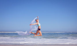 Fit woman jumping gracefully on the beach with scarf Royalty Free Stock Photo